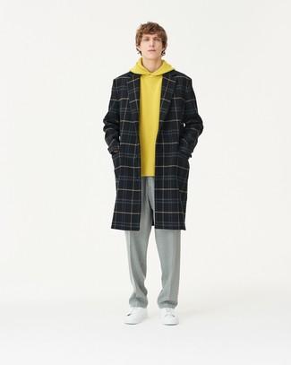 Модный лук: черное длинное пальто в шотландскую клетку, желтый худи, серые классические брюки, белые кожаные низкие кеды