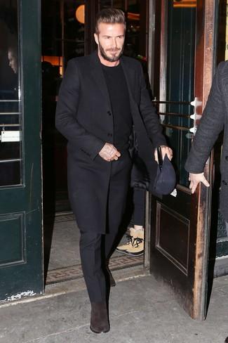 Как David Beckham носит Черное длинное пальто, Черный свитер с круглым вырезом, Черные классические брюки, Темно-коричневые замшевые ботинки челси