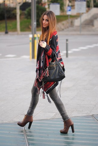 Как и с чем носить: черное пончо с принтом, серые джинсы скинни, коричневые кожаные ботильоны на шнуровке, черная кожаная большая сумка