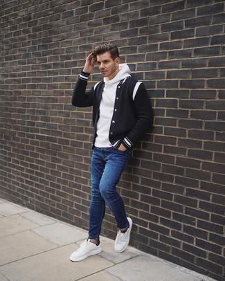 С чем носить синие зауженные джинсы мужчине: Если ты ценишь удобство и функциональность, черно-белая университетская куртка и синие зауженные джинсы — великолепный вариант для привлекательного повседневного мужского образа. Не прочь сделать лук немного элегантнее? Тогда в качестве обуви к этому луку, выбирай бело-черные низкие кеды из плотной ткани.