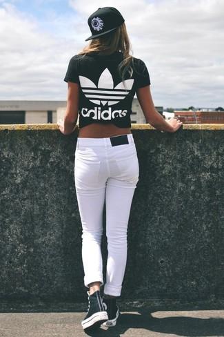 Как и с чем носить: черно-белая футболка с круглым вырезом с принтом, белые джинсы скинни, черно-белые высокие кеды, черно-белая кепка с принтом
