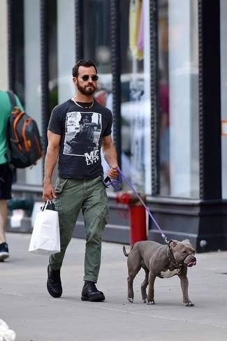 Как Justin Theroux носит Черно-белая футболка с круглым вырезом с принтом, Оливковые брюки карго, Черные кожаные повседневные ботинки