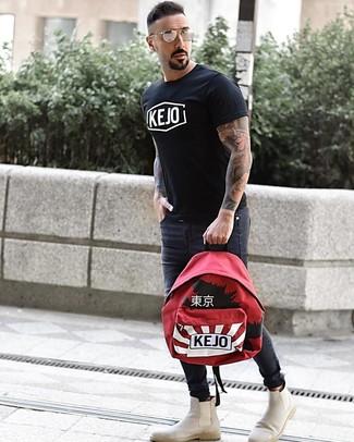 Как и с чем носить: черно-белая футболка с круглым вырезом с принтом, темно-серые зауженные джинсы, бежевые замшевые ботинки челси, красный рюкзак с принтом