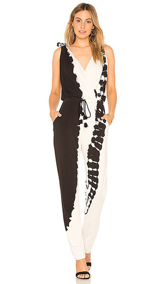 Как и с чем носить: черно-белый комбинезон c принтом тай-дай, черные замшевые босоножки на каблуке, золотые серьги