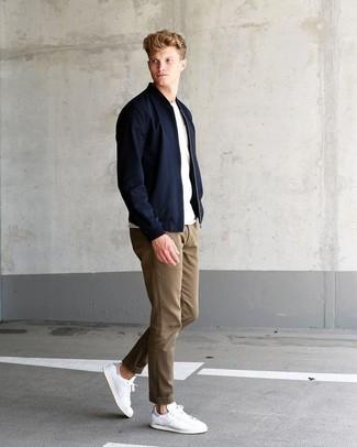 Как и с чем носить: черный бомбер, белая футболка с круглым вырезом, светло-коричневые брюки чинос, белые кожаные низкие кеды