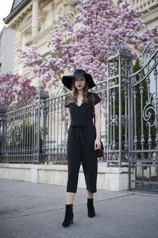 Как и с чем носить: черный комбинезон, черные замшевые ботильоны с украшением, пурпурная замшевая большая сумка, черная шляпа