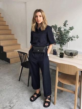 Как и с чем носить: черный комбинезон, черные кожаные сандалии на плоской подошве, черная кожаная поясная сумка