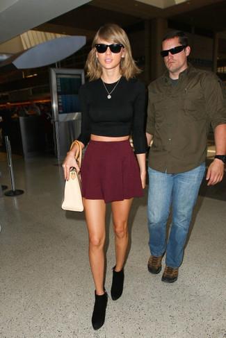 Как Taylor Swift носит Черный короткий свитер, Темно-красная короткая юбка-солнце, Черные замшевые ботильоны, Бежевая кожаная большая сумка