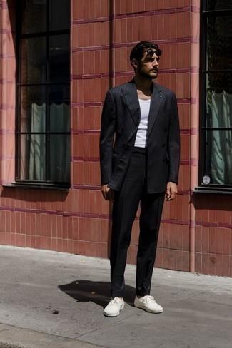 Черный костюм в вертикальную полоску: с чем носить и как сочетать: Если ты приписываешь себя к той немногочисленной категории мужчин, неплохо ориентирующихся в модных тенденциях, тебе придется по душе дуэт черного костюма в вертикальную полоску и белой майки. Любишь смелые сочетания? Можешь закончить свой образ белыми низкими кедами из плотной ткани.