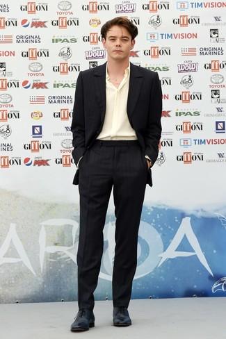 Как Charlie Heaton носит Черный костюм в вертикальную полоску, Желтая шелковая рубашка с длинным рукавом, Черные кожаные оксфорды