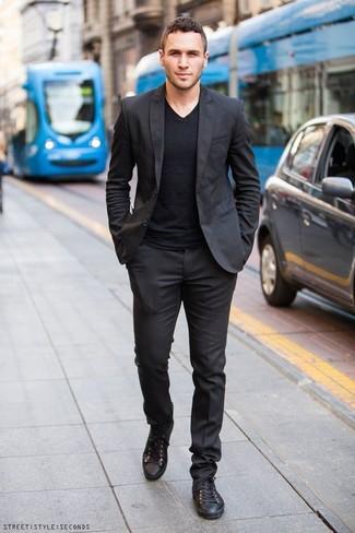 Черный костюм: с чем носить и как сочетать: Если ты принадлежишь к той редкой группе мужчин, неплохо разбирающихся в трендах, тебе подойдет лук из черного костюма и черной футболки с v-образным вырезом. Ты сможешь легко адаптировать такой ансамбль к повседневным нуждам, надев черными кожаными низкими кедами.