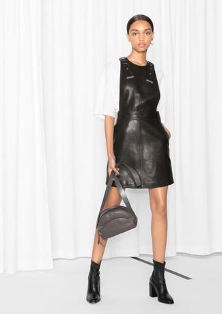 Как и с чем носить: черный кожаный сарафан, белая блуза с коротким рукавом, черные кожаные ботильоны, темно-серая кожаная поясная сумка