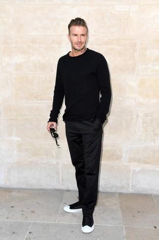 Как David Beckham носит Черный свитер с круглым вырезом, Черные брюки чинос, Черно-белые низкие кеды