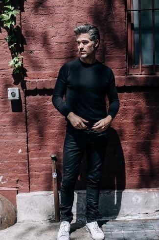 Модные мужские луки 2020 фото: Черный свитер с круглым вырезом и черные кожаные джинсы — прекрасная идея для несложного, но стильного мужского образа. Пара белых низких кед позволит сделать образ более законченным.