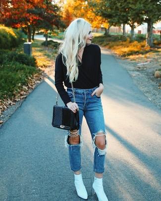 Как и с чем носить: черный свитер с v-образным вырезом, синие рваные джинсы-бойфренды, белые кожаные ботильоны, черная кожаная стеганая сумка-саквояж