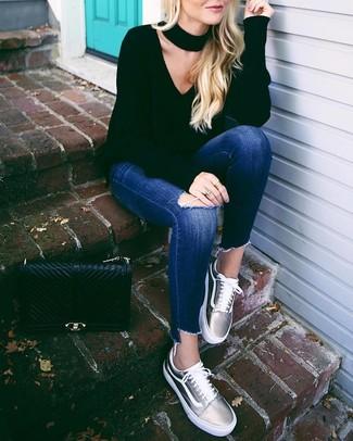 Как и с чем носить: черный свитер с v-образным вырезом, темно-синие рваные джинсы скинни, серебряные кожаные низкие кеды, черная кожаная стеганая сумка-саквояж
