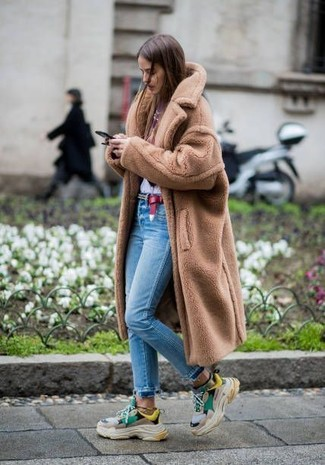 Как и с чем носить: светло-коричневая шуба, бело-красная футболка с круглым вырезом с принтом, голубые джинсы скинни, разноцветные кроссовки